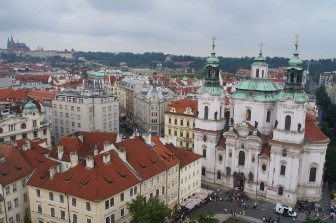 The Church of Saint Nicholas is in the foreground and the Castle Quarter across the Vltava River in the distance.
